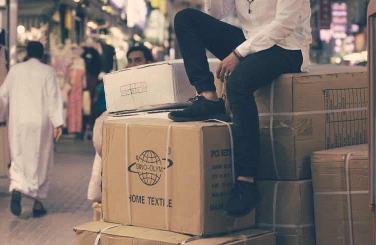 Man sipping a cup of coffee while sitting on a large stack of cardboard boxes in the street.