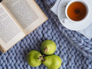 Book laid out beside a cup of tea and some fruit as self care routine