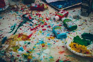 Paint bottles and paint splatter over a large white canvas for creativity for the mind
